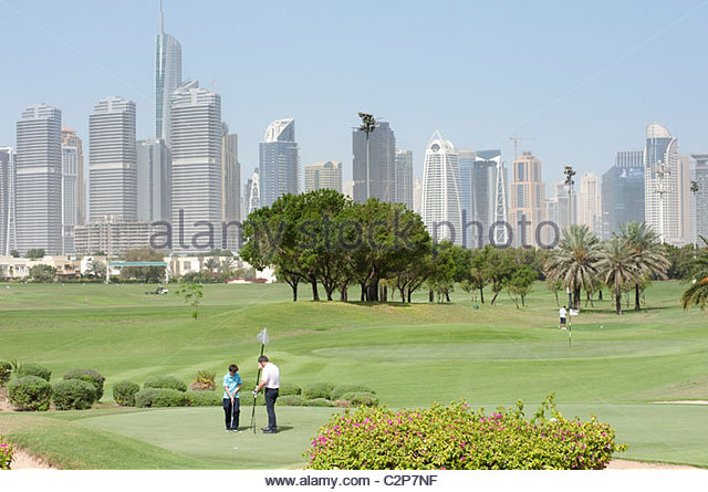 People playing golf on Montgomerie golf course with skyline of Jumeirah district in Dubai in distance United Arab - Stock Image
