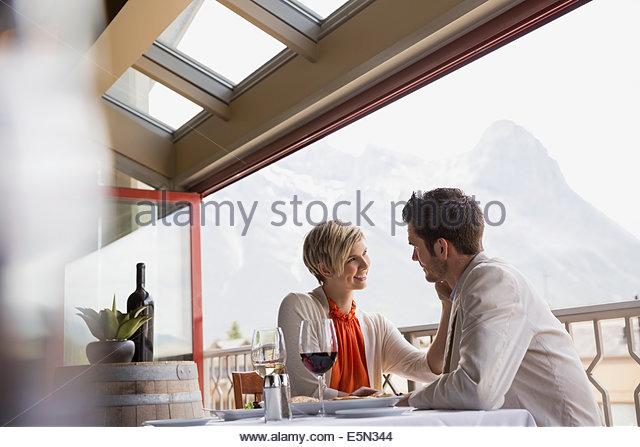 Romantic couple at restaurant table on balcony - Stock-Bilder