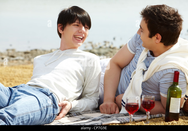 Laughing gay couple having a good time drinking red wine at beach - Stock Image