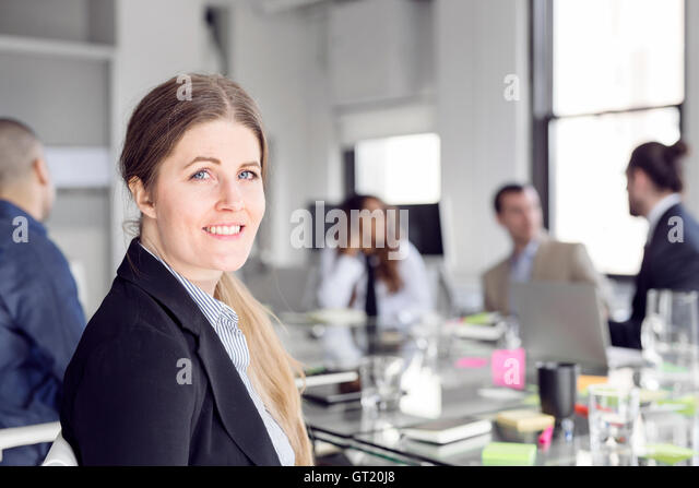 Close-up of smiling businesswoman sitting with colleagues at conference table - Stock-Bilder