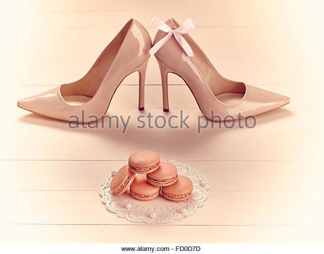 Woman essentials fashion accessories. Macarons french dessert, luxury beige shoes high heels, bow. Creative glamor - Stock Image
