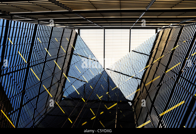 Modern building detail, metal structure reflecting on the glass - Stock Image