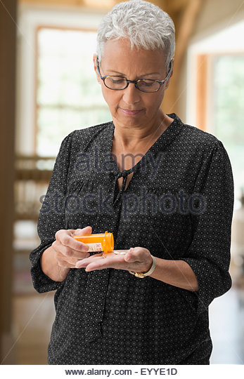 Mixed race woman holding medication pills - Stock Image