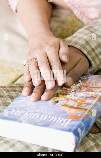 Close-up of couple's hands on the Bhagavad-Gita - Stock Image