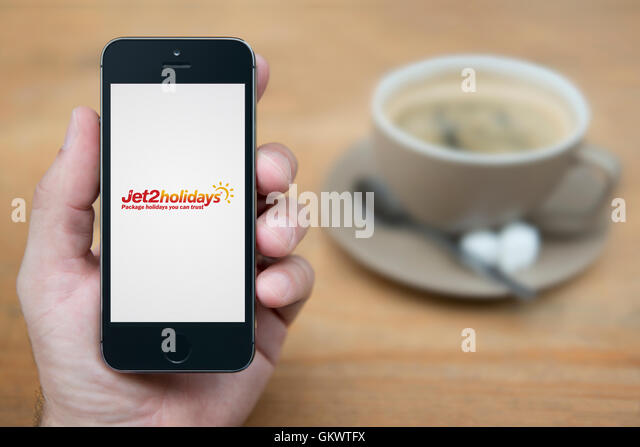A man looks at his iPhone which displays the Jet2 Holidays logo, while sat with a cup of coffee (Editorial use only). - Stock Image