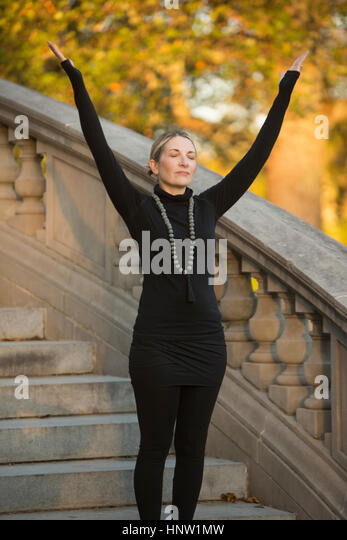 Caucasian woman meditating on staircase in park - Stock-Bilder