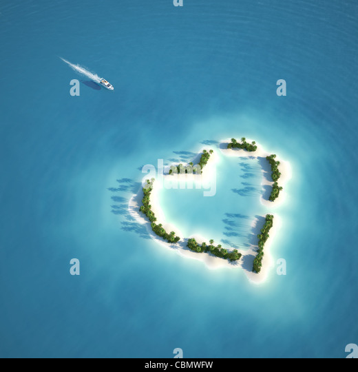 yacht heading to heart shaped island seen from the air concept for romantic vacation or valentines - Stock Image