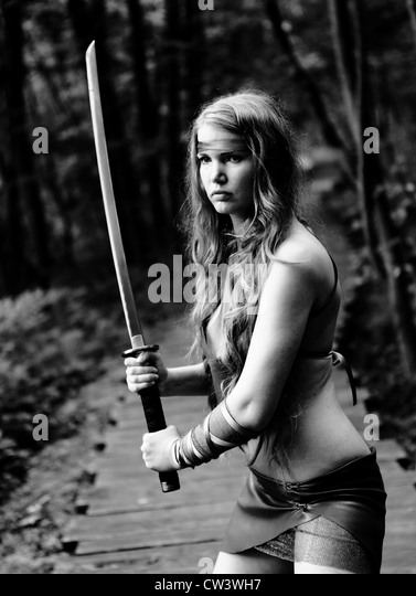 portrait of young woman with sword at forest - Stock-Bilder