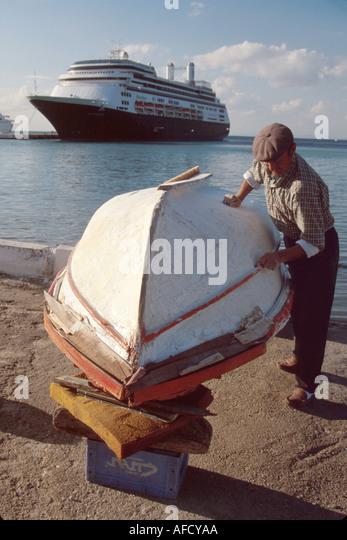 Turkey Aegean Coast Kusadasi fisherman sands his boat ms Rotterdam cruise ship beyond - Stock Image