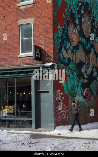 Canada, Quebec province, Montreal, Saint-Laurent boulevard, man passing in front of a cafe and a mural - Stock Image