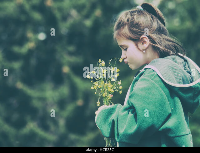 Little girl in nature smelling bunch of flowers - Stock Image