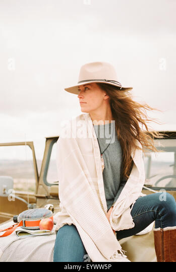 Woman wearing a hat sitting on the front of a jeep looking around her. - Stock-Bilder