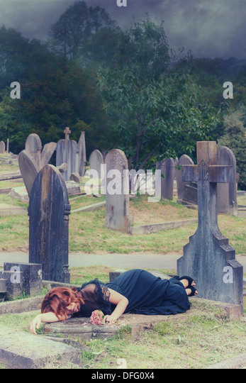 a woman is lying on a tomb with a bunch of flowers - Stock Image