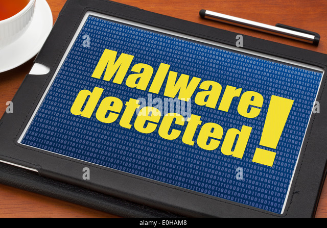 malware detected alert on a digital tablet with a cup of tea - Stock Image
