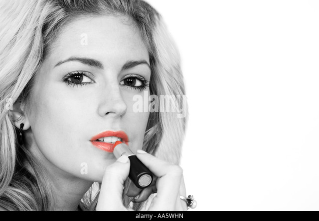Woman putting on lipstick black and white with red lips stock image