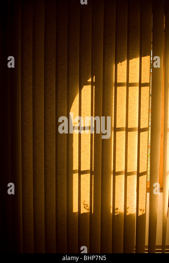 a moody image of a window's shadows falling onto vertical hanging blinds - Stock Image