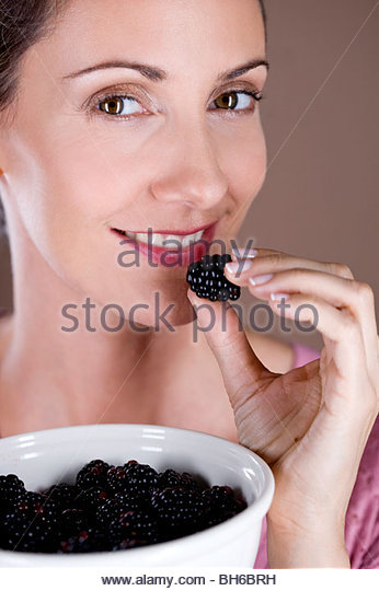 A mid adult woman eating a blackberry - Stock-Bilder