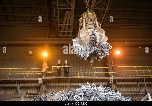 Steel workers watching mechanical grabber in steel foundry - Stock Image