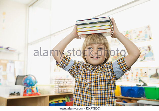 Boy holding stacked books on head - Stock Image