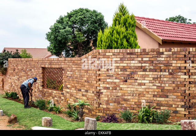 South Africa African Johannesburg Soweto Black man gardening landscape landscaping house home brick wall - Stock Image