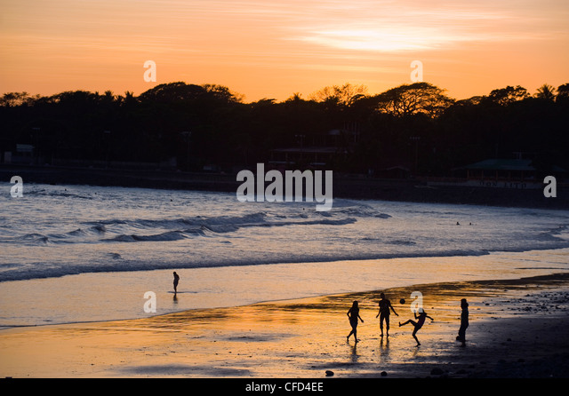 People playing football on the beach at La Libertad, Pacific Coast, El Salvador, Central America - Stock Image