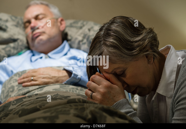 Senior woman praying for sick man sleeping in hospital bed - Stock-Bilder