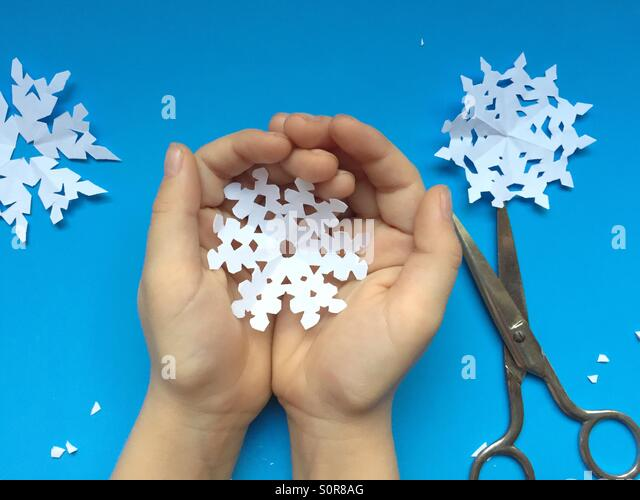 Child holds paper snowflake - Stock Image