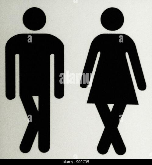 A sign showing male and female characters with crossed legs, needing to use a convenience. - Stock-Bilder