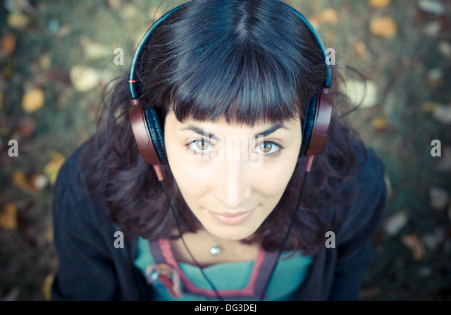 young beautiful woman listening to music at the park in autumn - Stock-Bilder