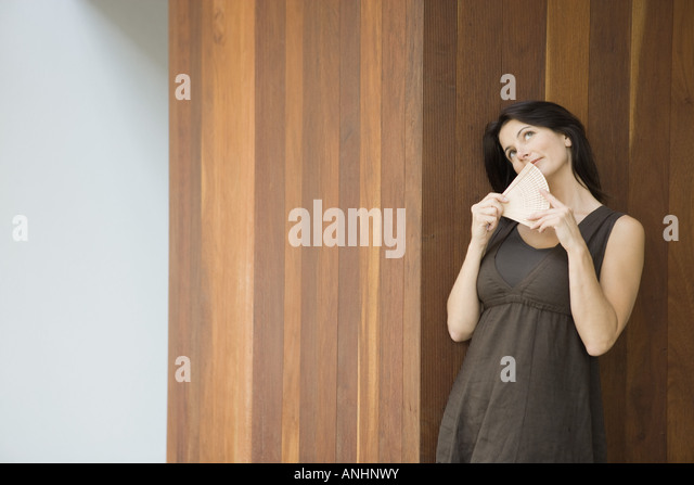 Woman leaning against wall, holding fan in front of face, looking up - Stock Image