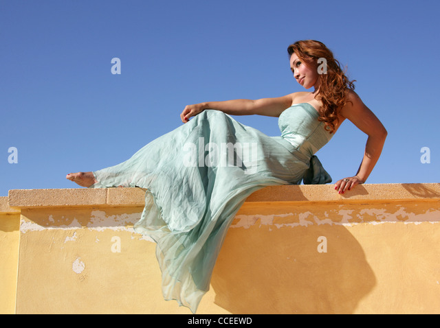 Indonesian Girl in a Turquoise Dress Laying on a Yellow Wall, Fuerteventura, Canary Islands, Spain. - Stock Image