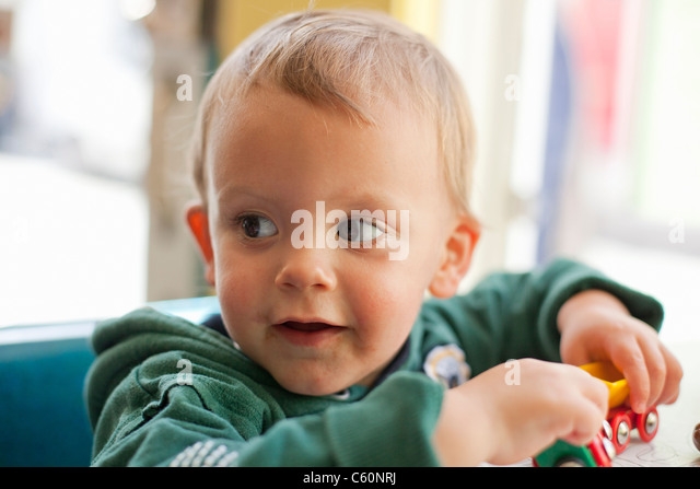 Baby boy playing with toy trains - Stock Image