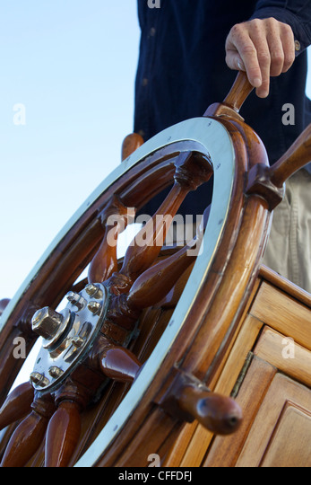 The captain keeps his hand on ship's wheel on board the sailing yacht - Stock Image
