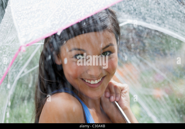 Beautiful young woman smiles towards the camera while holding an umbrella under a spray of water. Horizontal shot. - Stock Image