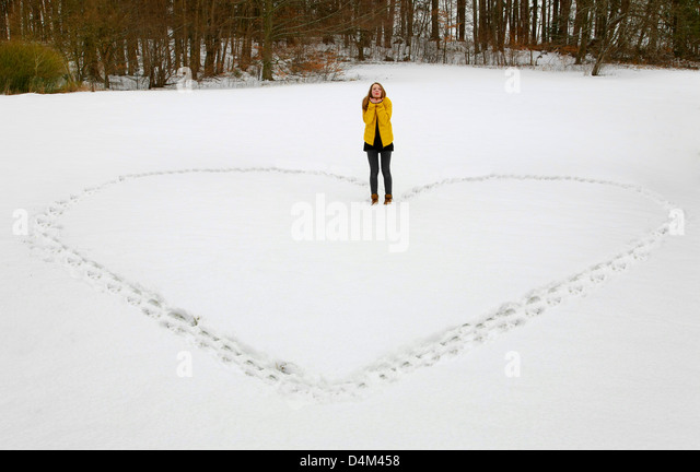 Woman making heart shape in snow - Stock Image