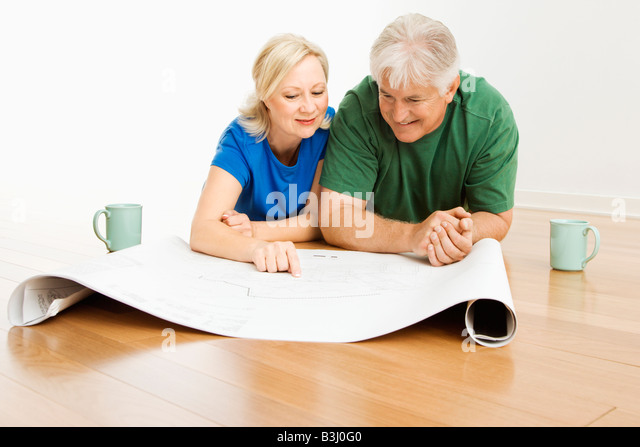 Middle aged couple lying on floor looking at and discussing architectural blueprints together - Stock-Bilder