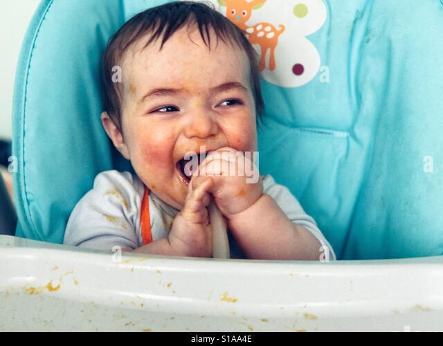 Baby eating messily - Stock-Bilder