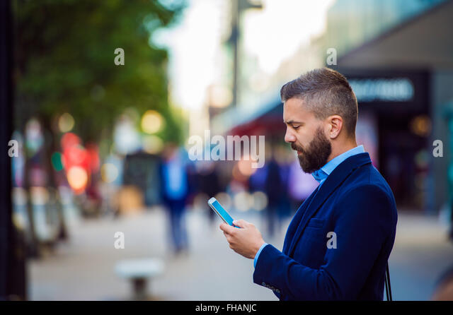 Hipster manager holding smartphone, texting outside in the stree - Stock-Bilder