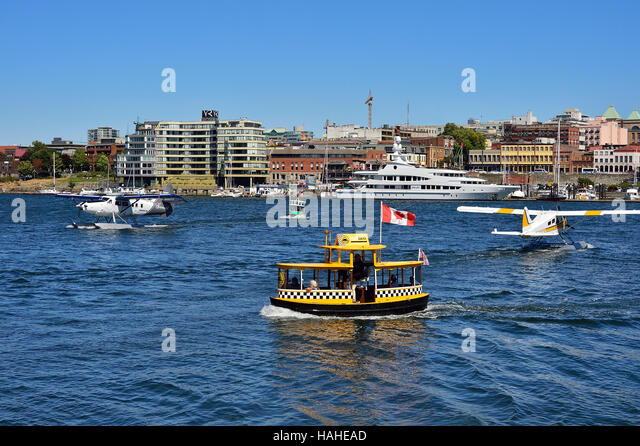 A very busy Victoria inner harbor with boats and float planes traveling to and frow. - Stock Image