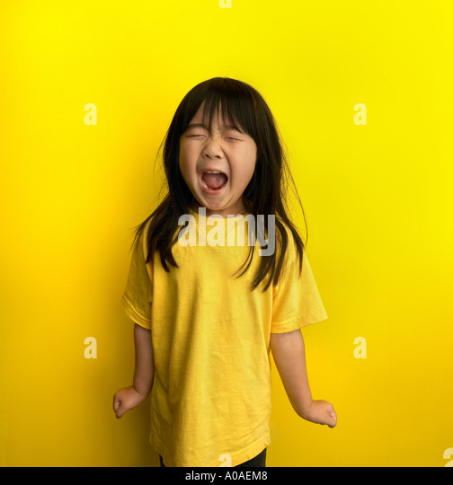 A little six year old girl in a yellow shirt in front of a yellow wall shouts with all her might! - Stock Image