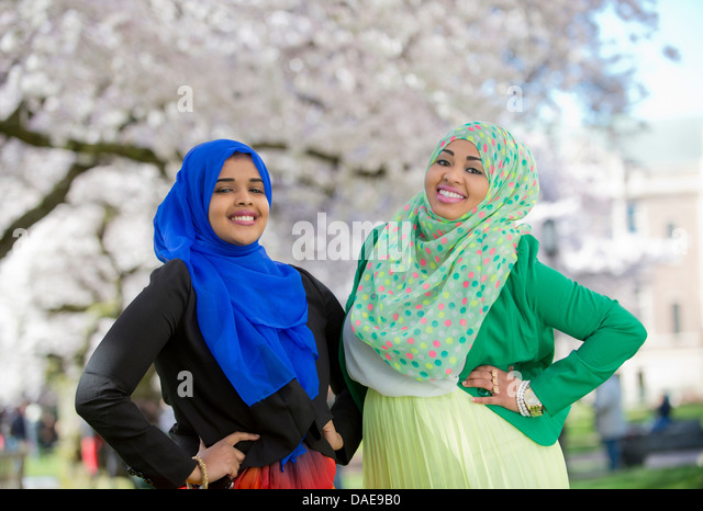 Portrait of two young females in park with hands on hips - Stock Image