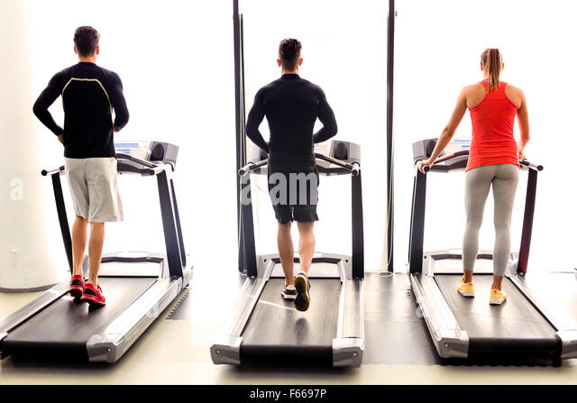 Group of young people using treadmills in a fitness center - Stock Image