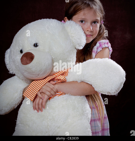 eight year old girl holding big teddy bear in her arms - Stock Image