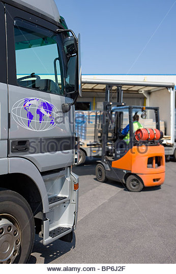 Forklift moving inventory on loading dock - Stock Image