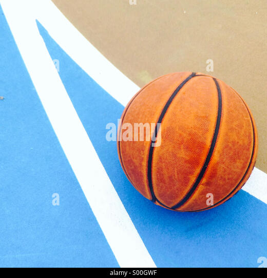 Basketball on an outdoor court. - Stock Image