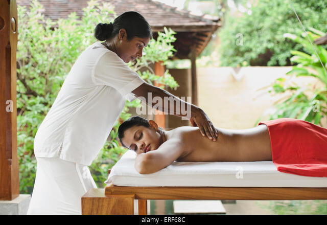 A woman receives a Deep Tissue Massage at the Sahana Spa, Saman Villas, Aturuwella, Bentota, Sri Lanka. - Stock Image
