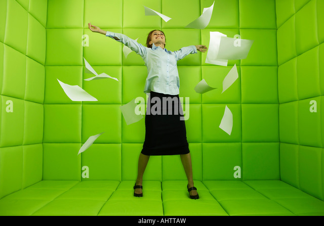 Woman throwing papers around green padded cell - Stock-Bilder