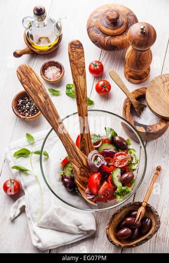 Fresh vegetable salad and olive wood tableware - Stock Image
