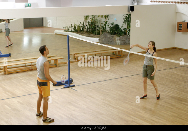 couple playing badminton in a badminton hall. - Stock Image