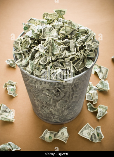 Waste paper basket with crumpled money - Stock-Bilder